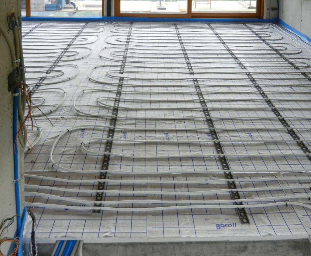 Die Fussbodenheizung ist komplett verlegt. Vorne ist der Treppenausschnitt in der Decke, der Elektriker hat schon einige Kabel in die Leerrohre gezogen. 19.09.2014