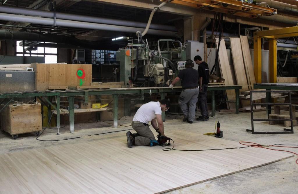 Hier wird der letzte Arbeitsschritt gezeigt. Die an sich fertige Dreischichtplatte liegt auf dem Boden und wird noch auf letzte Fehlstellen, Astlöcher u.ä. geprüft.