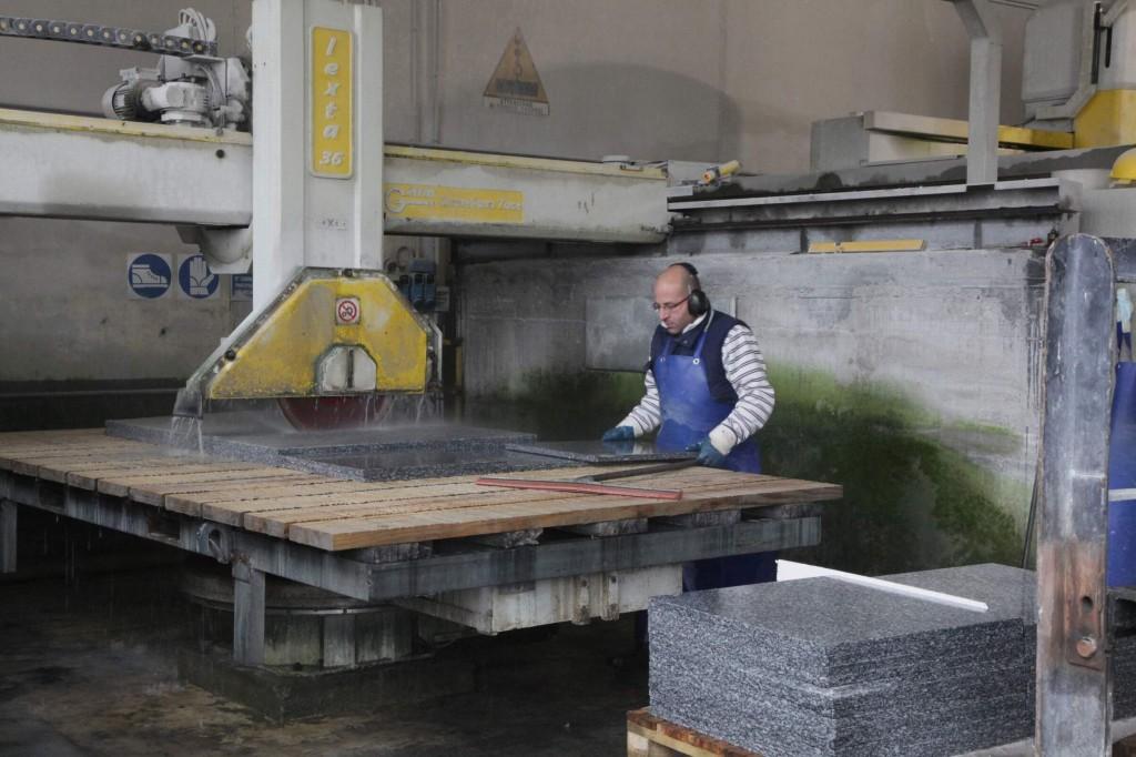 Hier erfolgt der zweite Arbeitsschritt. Die von der grossen Kreissäge abgetrennten Scheiben werden flach auf den Schneidetisch gelegt. Dann werden aus diesen Platten mit der deutlich kleineren Kreissäge die eigentlichen Steinplatten herausgetrennt.
