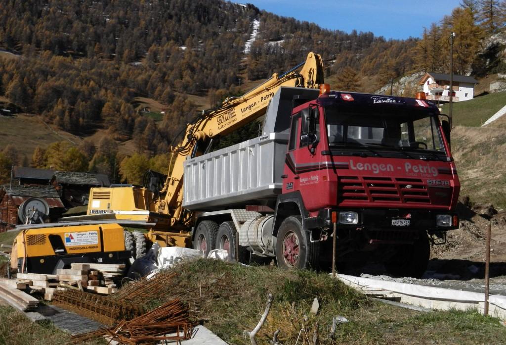 Ein Teil des Baugrubenaushubs wird abgefahren. Typisch für Bauarbeiten im Bergebiet sind wegen ihrer besonderen Geländegängigkeit die inzwischen nicht mehr gebauten LKW von Steyr.