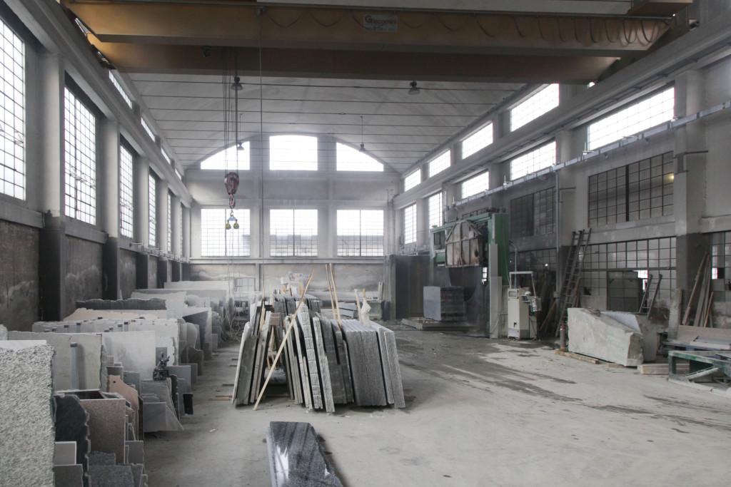 Nochmals ein Blick in die Halle. Im hinteren Bereich steht als das wichtigste Werkzeug eine gewaltige Kreissäge, die die Blöcke in Scheiben schneidet. Die Scheiben werden links zwischengelagert.