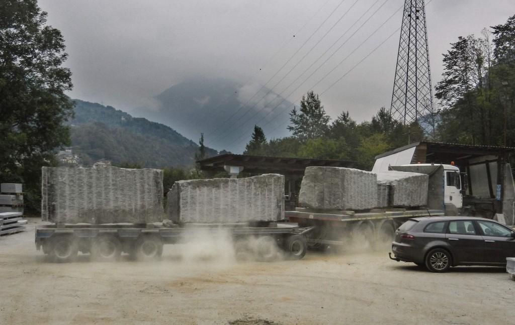 Ein LKW mit 5 grossen Granitblöcken donnert über den Hof der Steinverarbeitung.